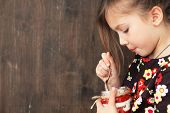 Portrait of a child eating sweet homemade dessert with berries