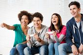 picture of indoor games  - Happy Group Of Young Friends Playing Video Games At Home - JPG