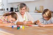 Granny and her grandchildren drawing seriously in kitchen