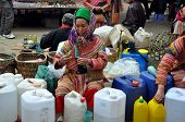 A Black H'mong minority woman selling rice wine in Bac Ha market, Vietnam