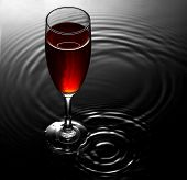 Red wine glass on water ripples background