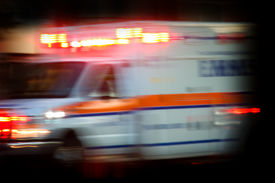 stock photo of emergency light  - Ambulance rushing away from scene with lights flashing - JPG