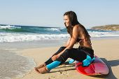 stock photo of dress-making  - A beuatiful surfer girl making preparation for a surf session - JPG