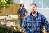 Portrait of mid adult manual worker in casual shirt standing with coworker in background at construc