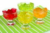 stock photo of jello  - Tasty jelly cubes in bowls on table on white background - JPG