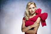 stock photo of hair bow  - young and sexy beautiful blond woman in red dress with nice hair style and a big bow on shoulder - JPG