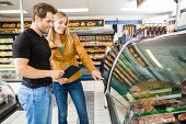 Couple choosing meat from display cabinet at butcher's shop