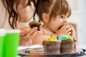 Cropped image of mother holding cupcake with girl eating cake at birthday party