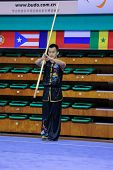 KUALA LUMPUR - NOV 03: Malaysia's Ho Mun Hua performs with a staff in the Men's 'Nangun' Event at the 12th World Wushu Championship on November 03, 2013 in Kuala Lumpur, Malaysia.