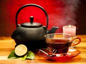 image of teapot  - a cup of black tea with teapot in the background - JPG