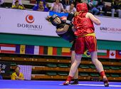 KUALA LUMPUR - NOV 03: Ukraine's Nadiia Chorna (red) punches China's Meng Zin in the Women's < 70kg 'Sanda' event at the 12th World Wushu Championship on November 03, 2013 in Kuala Lumpur, Malaysia.
