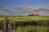 pic of hever  - Lighthouse and a small bridge in the salt meadows at the germany north sea coast - JPG
