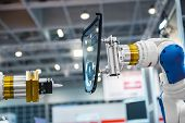 foto of robotics  - Robot arm in a factory working for the humans - JPG