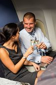 Smart couple business travel by airplane toasting champagne passengers flight