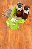 Ginkgo biloba leaves and medicine bottles on wooden background