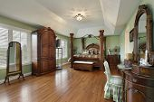 Large master bedroom with wood framed bed