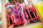 Happy kids in winterwear having fun on playground