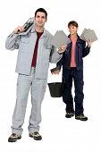 Tile fitters holding up their building supplies and tools