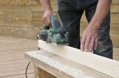 stock photo of carpenter  - The carpenter processes a surface of wooden object - JPG