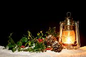 An oil filled lantern sitting in snow with holly, ivy and pine cones illuminated by the glow of the