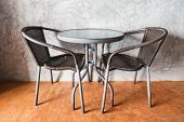 A Table And Chairs On The Brown Concrete Floor