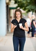stock photo of status  - Mid adult woman with disposable coffee cup using smartphone while walking on pavement - JPG