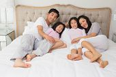 Full length portrait of a happy family of four lying in bed at home