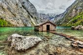 High dynamic range (HDR) image of boat dock hangar on Obersee mountain lake in Alps. Bavaria, German
