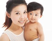 foto of cuddle  - Happy mother holding smiling child baby in studio - JPG