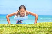 Push-ups fitness woman doing pushups outside on beach on grass. Fit female sport model girl training