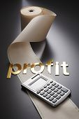 adding machine tape  and calculator with word profit