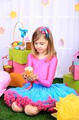 Beautiful small girl in petty skirt holding Easter cake on decorative background