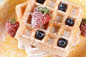Closeup of fruity waffles covered with powdered sugar. Fresh blueberries and strawberries on a stack