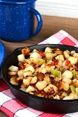 Closeup of a cast iron skillet full of breakfast potatoes. Vertical format with shallow depth of field.