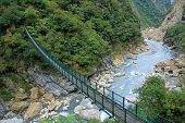 TAIWAN - DECEMBER 28 : A long suspension footbridge crossing the river at Taroko National Park on De