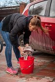 Young Woman Wringing Rag While Washing Car Outdoor