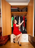 Elegant Woman Looking At Dresses In Big Wardrobe
