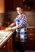 Smiling Woman Cutting Bread On Wooden Cutting Board