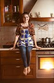 Smiling Woman Sitting On Tabletop While Baking In Oven
