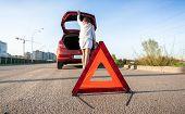 Woman Looking In Trunk Of Broken Car