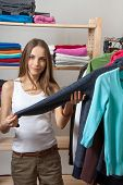 young woman chooses clothes in the shop