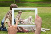 Hand holding tablet pc showing cute siblings sitting with pet dog in park