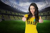 Pretty football fan in brasil tshirt in a large football stadium with fans in yellow