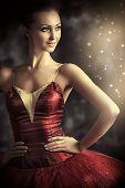Beautiful bellet dancer posing at studio over vintage background.