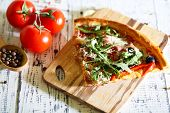 Piece of pizza with arugula on cutting board, color wooden background
