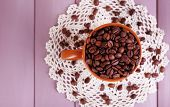 Cup full of coffee beans on color wooden background