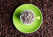 image of coffee grounds  - Cup full of green coffee beans on brown coffee beans background - JPG