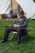 Civil War Man with a Musket Rifle at a Civil War Encampment