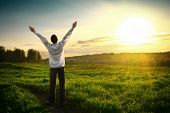 foto of rapture  - Happy Young man with hands up on sunset background - JPG