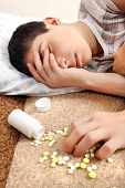 stock photo of home remedy  - Teenager sleeps near the Pills on the Bed at the Home - JPG
